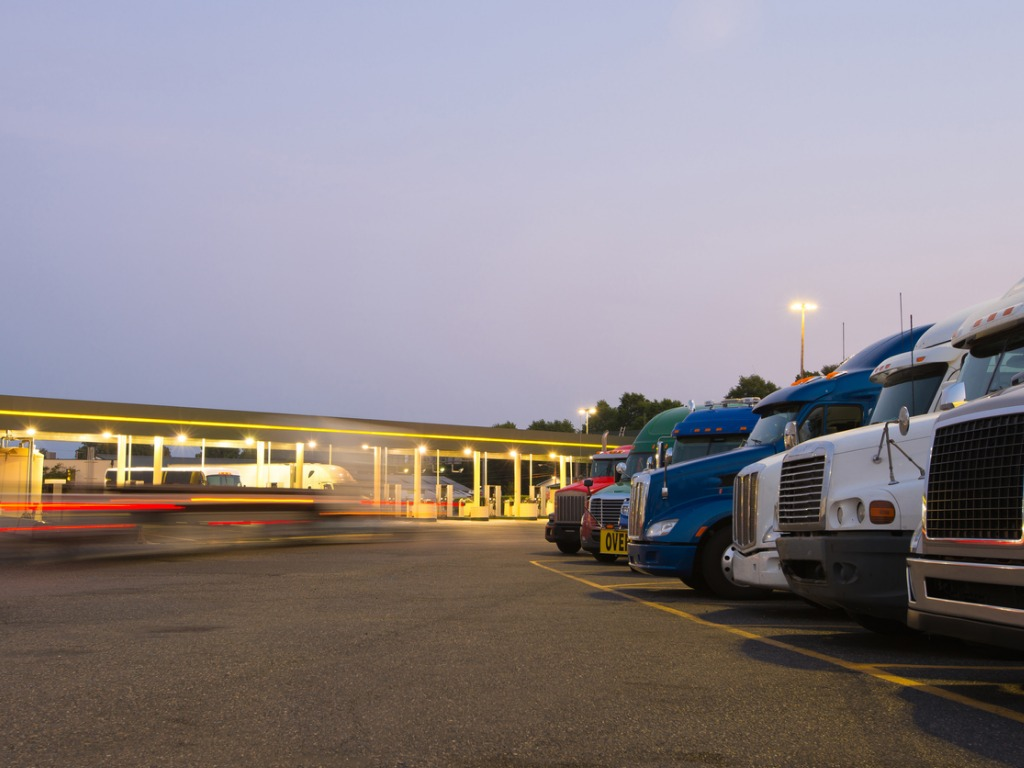 evening-truck-stop-lights-of-number-of-trucks-in-parking-picture-id514852941